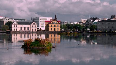 Beautiful reflection of buildings in lake Tjornin. in Reykjavik in summer. Iceland, Europe.