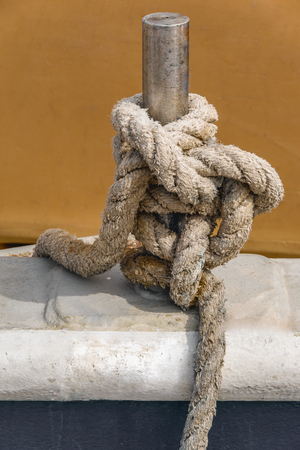 Close up view of old natural rope tied around stainless steel pillar on a fisherman boat.