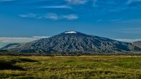 Panoramic view of black volcano Snæfellsjökull with blue sky above and green dry grass below . West Iceland, Europe. Reklamní fotografie