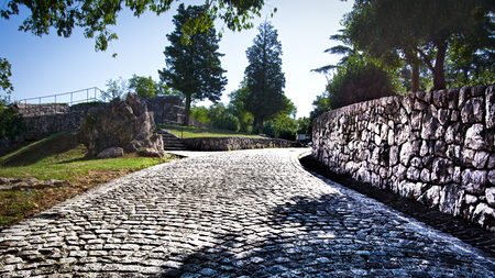 Close up view of cobblestone road leading from Trsat castle to green forest. Rijeka, Croatia,Europe.