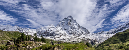 Panoramic view of the south face of the Matterhorn, view from the Breuil-Cervinia village.Green meadow in the front and blue sky with white clouds above mountains.Summer in the Alps, Italy, Europe.