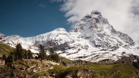 Landscape view of the south face of the Matterhorn, view from Cervinia village.Green meadow in the front and blue sky with white clouds above mountains.Summer in the Alps, Italy, Europe.