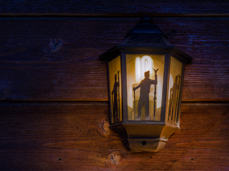 Close up view of one street lamp on a wooden brown wall lighting with yellow light during the blue winter night.