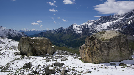 Close up view of two big rocks with beautiful mountain landscape in the background.Summer in the Pennine Alps, Valle dAosta, Italy, Europe.