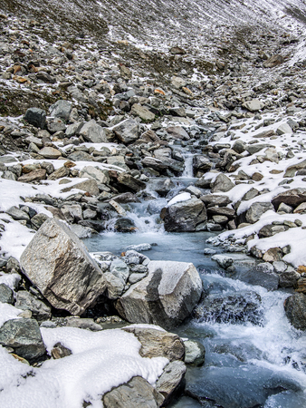 Beautiful view of one mountain river with small waterfalls and snow around. Summer in Valle dAosta, Italy, Europe.