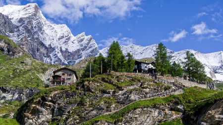Close up view of traditional rural huts in the Pennine Alps. Green grass around, blue sky with white clouds above and Matterhorn behind. Summer in the Pennine Alps, Valle dAosta, Italy, Europe.