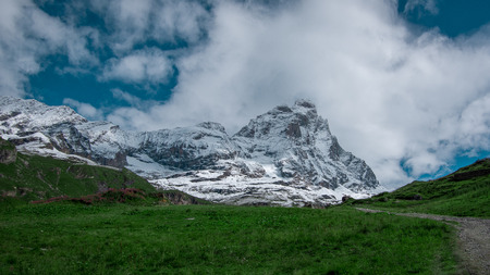 Landscape view of the south face of the Matterhorn, view from Breuil-Cervinia.Green meadow in the front, blue sky with white clouds above. Summer in the Pennine Alps, Valle dAosta, Italy, Europe.