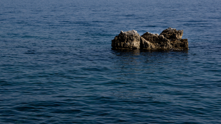 Close up view of one gray rock surrounded by blue sea. Use for background. Autumn in Opatija, Croatia, Europe.