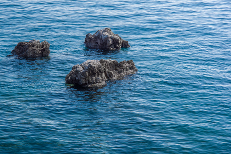 Close up view of three gray rocks surrounded by blue sea. Use for background. Autumn in Opatija, Croatia, Europe.