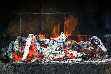 Close up front view of fire burning in a brick barbecue.