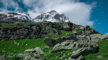 Close up view of the south face of the Matterhorn.Green meadow in the front, blue sky with white clouds above. Summer in the Pennine Alps, Valle dAosta, Italy, Europe.