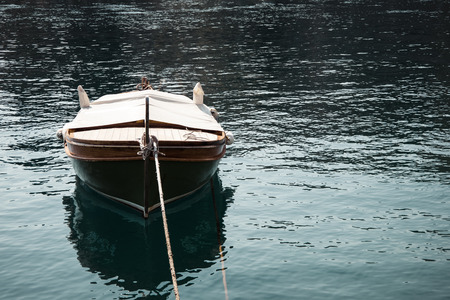 Landscape view of one brown wooden boat tied in the front. Surrounded with a blue sea with small waves reflecting sunlight. Autumn in Opatija, Croatia, Europe.