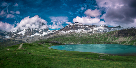 Panoramic view of the south face of the Matterhorn, view from Plan Maison.Green meadow and a crystal blue lake in the front, blue sky with white clouds above and mountains in the background. Summer in the Pennine Alps, Valle dAosta, Italy, Europe.