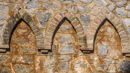 Close up view of three bricks ornaments integrated into the orange stone wall.Use for background. Opatija Croatia, Europe.