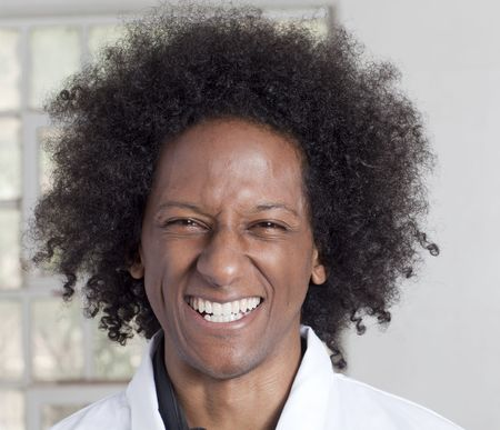 A young black man with an afro making various facial expressions while wearing a lab coat