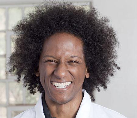 Un joven negro con un afro haciendo diversas expresiones faciales mientras llevaba una bata de laboratorio  Foto de archivo