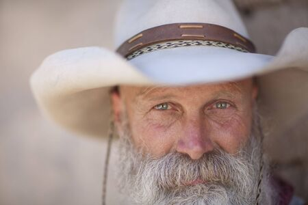 A cowboy with a white beard looking at camera