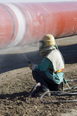 preperation: A worker sandblasting the weld in preperation for coating during pipeline construction