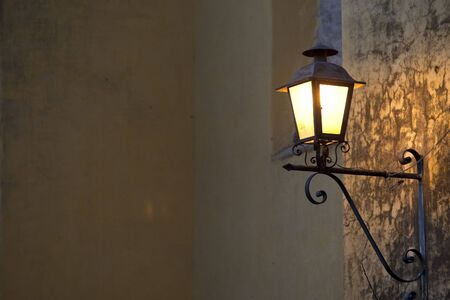 A spanish style lamp mounted to a concrete wall glows in the evening Stock Photo