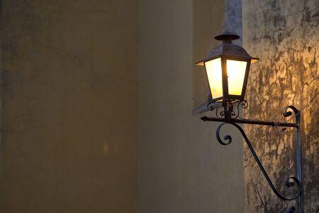 Una l�mpara de estilo espa�ol montada para un hormig�n brilla en la noche de la pared