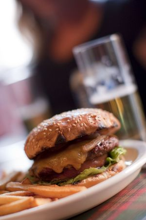 A chesseburger and beer on a table Stock Photo