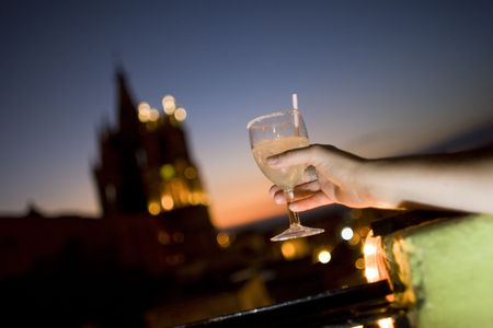 A womans hand holding a margarita on a balcony in Mexico overlooking San Miguel de Allende Stock Photo