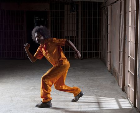 A black man with an afro making various faces and gestures inside a federal prison