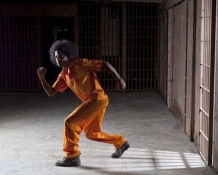 Un hombre negro con un afro haciendo varias caras y gestos dentro de una prisi�n federal