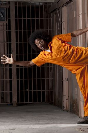 A black man with an afro making vaus faces and gestures inside a federal prison Stock Photo - 6649683