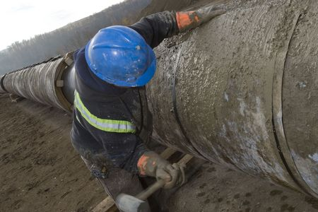 A pipeline construction worker hammering on a pipe Stock Photo