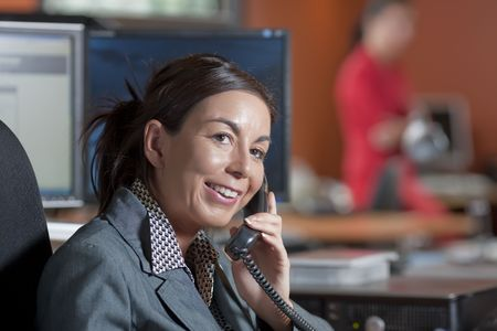 A female office worker talking on the telephone