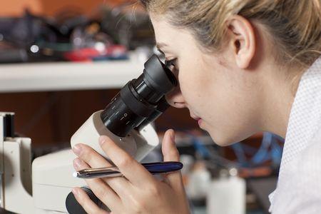 Un investigador femenino estudiando un microscopio  Foto de archivo
