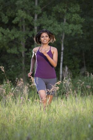 An ethnic looking woman in her 20s running