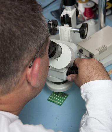 Male scientist using a microscope