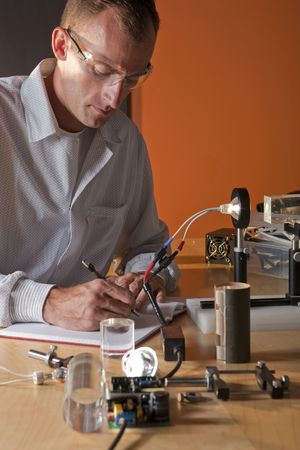 Un investigador en una bata de laboratorio haciendo notas sobre un experimento  Foto de archivo