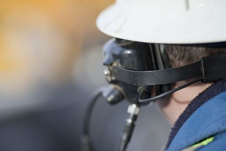 A view of an industrial worker from behind while wearing headphones and a hard hat