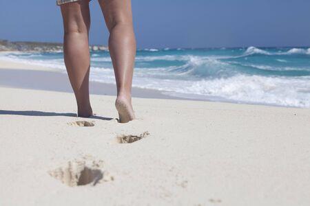 Vista de una piernas womans, vistiendo pantalones cortos en la playa en el Caribe