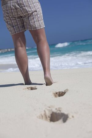 View of a womans legs, wearing shorts on the beach in the caribbean