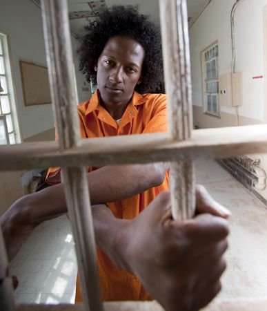 prisoner man: A black man with an afro making various faces and gestures inside a federal prison