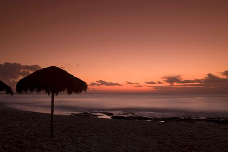 A palapa hut on the beach at sunset in Playa del Carmen Mexico