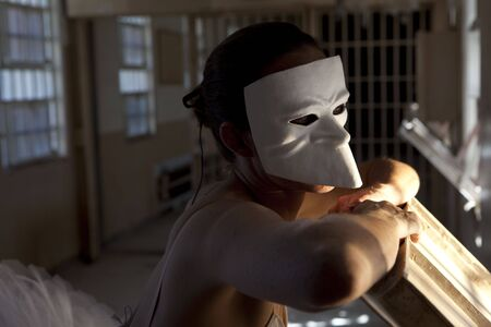 A dancer in a mask, looking out a window of a prison hallway Stock Photo