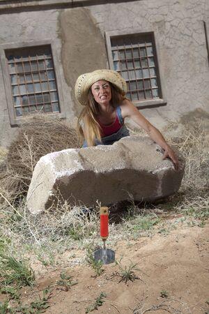 Una mujer en guardapolvos de mezclilla levantar una roca imposiblemente grande encima de su cabeza  Foto de archivo