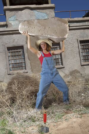 A woman in denim coveralls lifting an impossibly large rock over her head