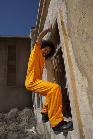 An african american male in orange prison coveralls escapes from prison by climbing a wall Stock Photo