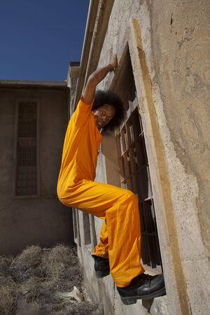 Un hombre africano americano en guardapolvos de naranja prisi�n se escapa de la c�rcel por un muro de escalada