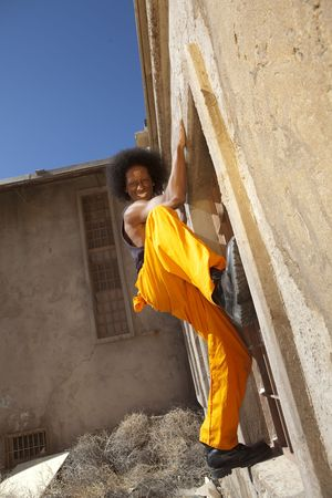 An african american male in orange prison coveralls escapes from prison by climbing a wall Stock Photo - 6650060