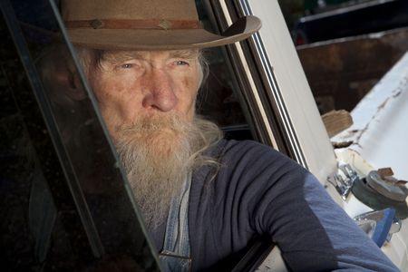 Un anciano con una barba blanca conduciendo una camioneta pickup y mirando por la ventana