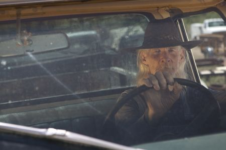 An elderly man with a white beard driving a pickup truck and staring out the window