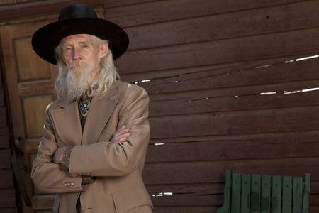 An elderly western genetleman in a suit and cowboy hat
