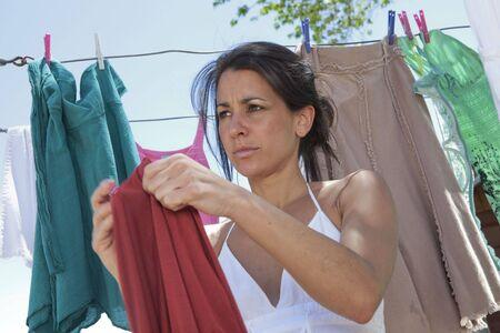 Una mujer joven atractiva colgando de la lavander�a.